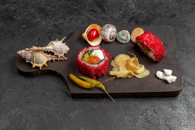 Vista frontal de uma saborosa refeição de sushi em fatias de rolos de peixe com conchas na parede cinza