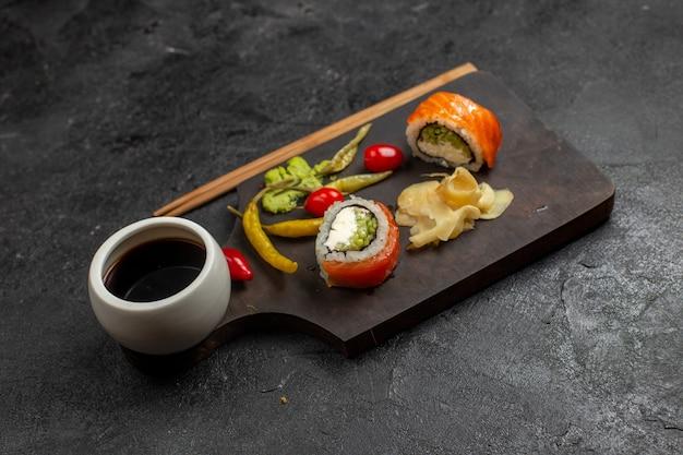 Vista frontal de uma saborosa refeição de sushi em fatias de rolos de peixe com molho na parede cinza