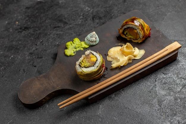 Vista frontal de uma saborosa refeição de sushi em fatias de rolos de peixe com wassabi verde e palitos na parede cinza
