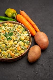 Vista frontal de uma saborosa salada com legumes frescos na superfície escura