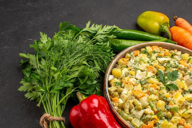 Vista frontal de uma saborosa salada com verduras e legumes na superfície escura