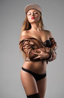 Vista frontal de uma senhora atraente com corpo perfeito fazendo beicinho sedutoramente. linda garota vestindo jaqueta de couro e roupa íntima sexy. isolado no fundo azul do estúdio. conceito de beleza e sexualidade.