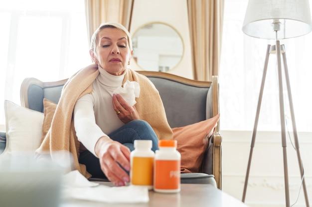 Vista frontal de uma senhora idosa pegando um frasco de comprimidos na mesa