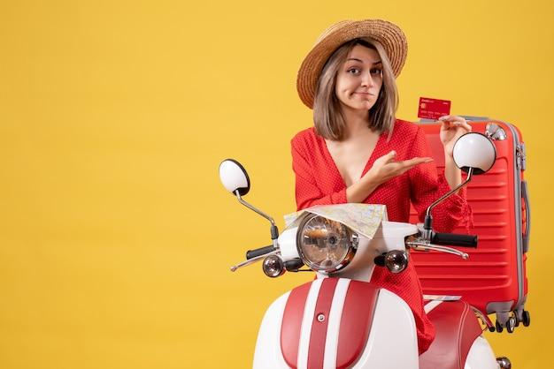 Vista frontal de uma senhora loira de vestido vermelho segurando um cartão de descontos perto de um ciclomotor