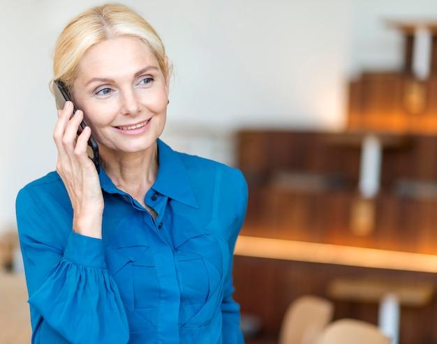 Vista frontal de uma sorridente mulher de negócios mais velha falando ao telefone