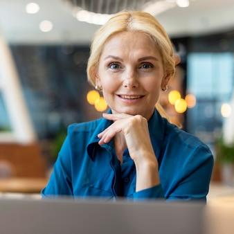Vista frontal de uma sorridente mulher de negócios mais velha posando em uma lanchonete