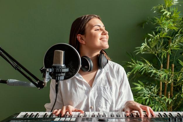 Vista frontal de uma sorridente musicista tocando teclado de piano dentro de casa