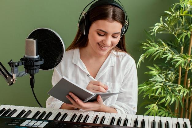 Vista frontal de uma sorridente musicista tocando teclado de piano e escrevendo músicas durante a gravação