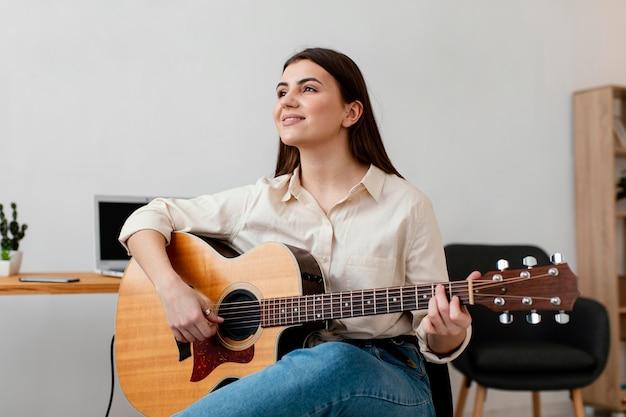 Vista frontal de uma sorridente musicista tocando violão
