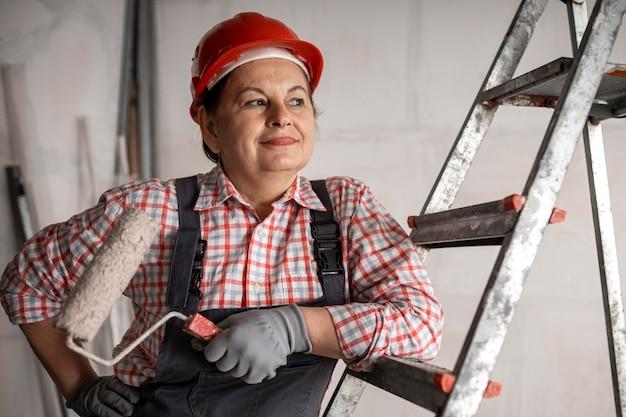 Vista frontal de uma sorridente trabalhadora da construção civil com rolo de pintura