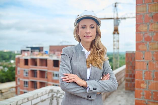 Vista frontal de uma supervisora de construção serena e determinada em um capacete de segurança inspecionando um novo objeto de construção