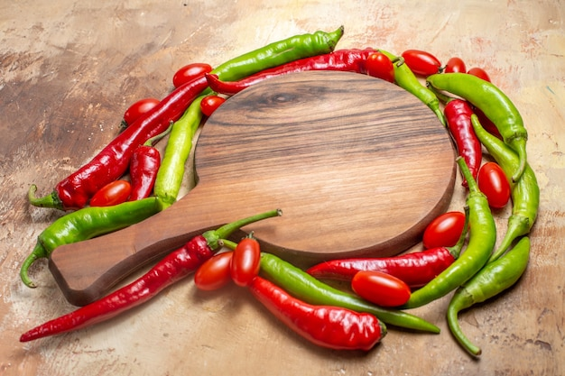 Vista frontal de uma tábua de cortar cercada por pimentas e tomates cereja em âmbar
