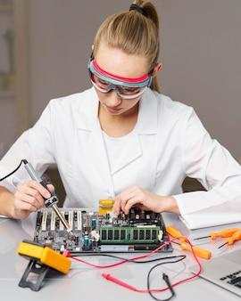 Vista frontal de uma técnica com ferro de solda e placa eletrônica