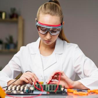 Vista frontal de uma técnica com ferro de solda e placa-mãe de eletrônicos