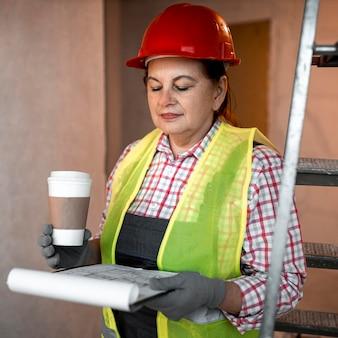 Vista frontal de uma trabalhadora da construção civil com café e planta