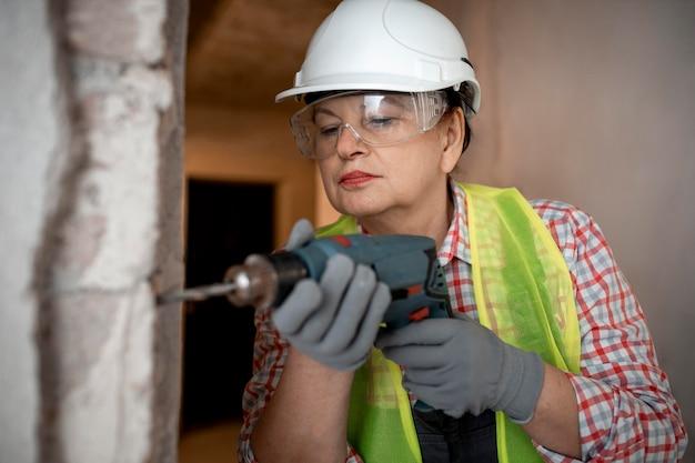 Vista frontal de uma trabalhadora da construção civil com capacete e furadeira elétrica
