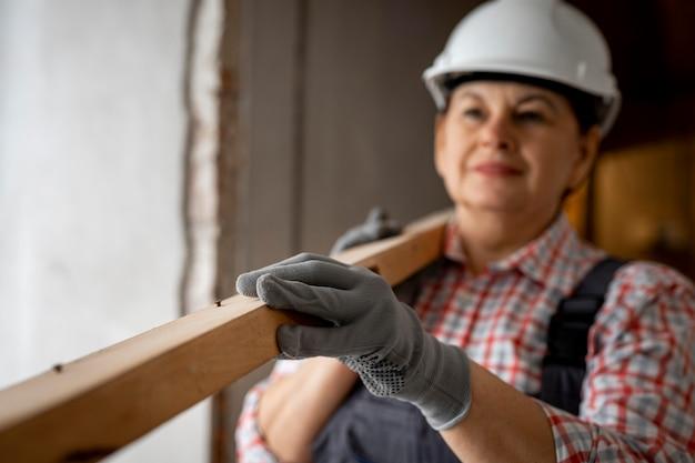 Vista frontal de uma trabalhadora da construção civil com capacete e peça de madeira