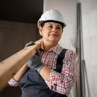 Vista frontal de uma trabalhadora da construção civil com capacete