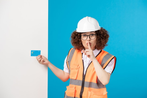 Vista frontal de uma trabalhadora de uniforme com cartão de crédito azul na parede azul