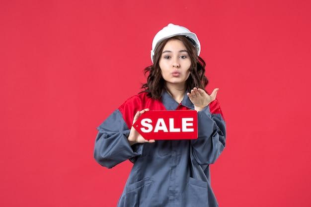 Vista frontal de uma trabalhadora de uniforme usando capacete mostrando o ícone de venda e enviando um gesto de beijo na parede vermelha isolada