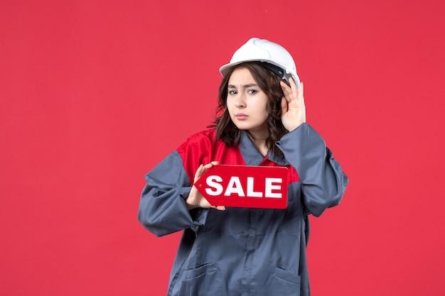 Vista frontal de uma trabalhadora de uniforme usando capacete mostrando o ícone de venda e ouvindo a última fofoca na parede vermelha isolada