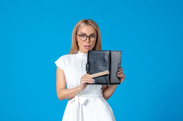 Vista frontal de uma trabalhadora em um lindo vestido branco com bloco de notas na parede azul