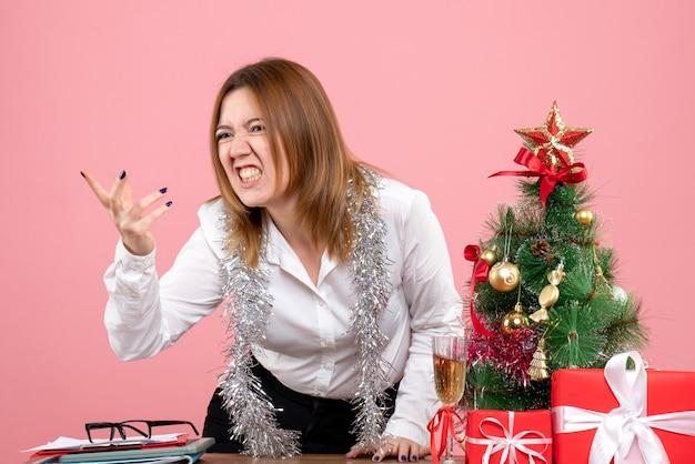 Vista frontal de uma trabalhadora perto de presentes de natal discutindo na rosa