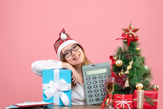 Vista frontal de uma trabalhadora segurando calculadora em torno de presentes em rosa