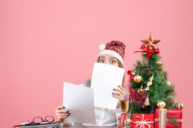Vista frontal de uma trabalhadora segurando documentos rosa