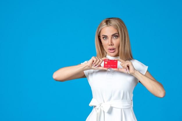 Vista frontal de uma trabalhadora segurando um cartão vermelho do banco na parede azul