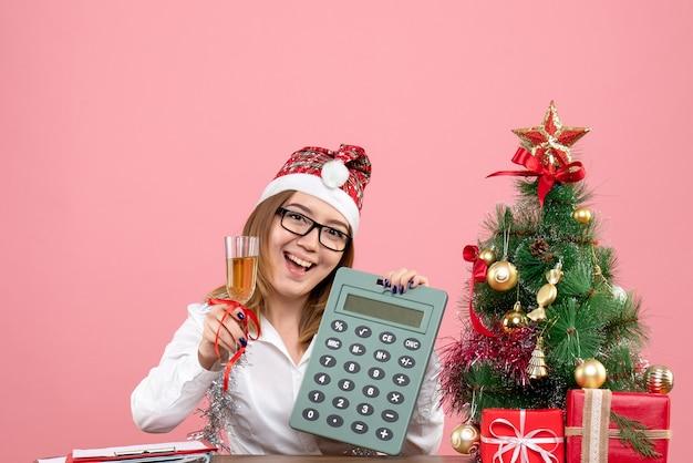 Vista frontal de uma trabalhadora segurando uma calculadora rosa