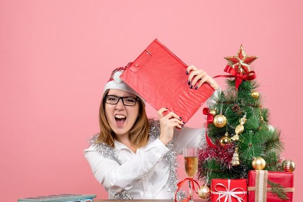 Vista frontal de uma trabalhadora segurando uma nota de arquivo rosa