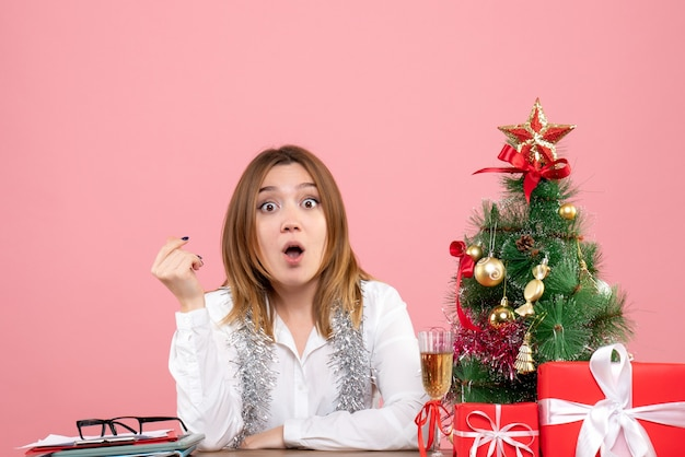 Vista frontal de uma trabalhadora sentada atrás de sua mesa com presentes em rosa