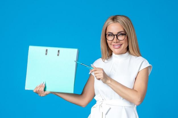 Vista frontal de uma trabalhadora vestida de branco segurando uma pasta azul na parede azul