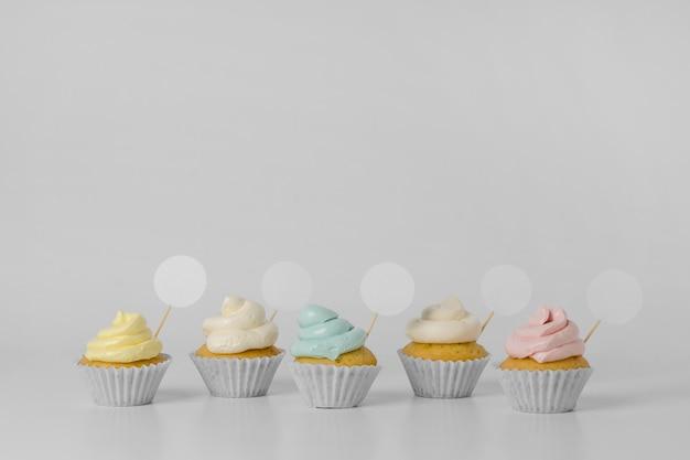 Vista frontal de uma variedade de cupcakes com embalagem e espaço de cópia