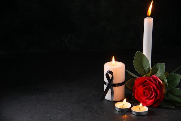 Vista frontal de uma vela acesa com uma flor vermelha na superfície escura