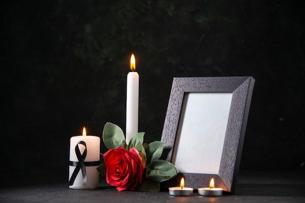 Vista frontal de uma vela branca com moldura e flor na mesa escura.