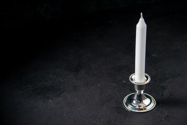Vista frontal de uma vela longa branca na parede escura