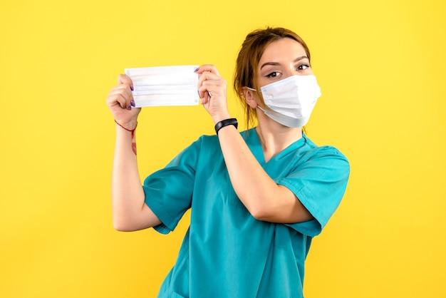 Vista frontal de uma veterinária com máscara na parede amarela