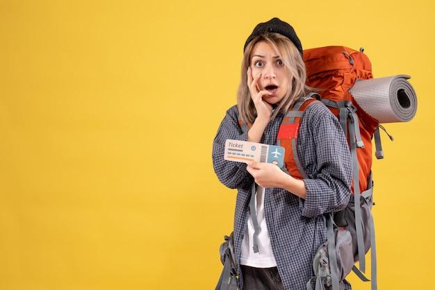 Vista frontal de uma viajante confusa com uma mochila segurando o ingresso