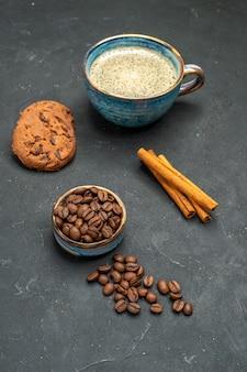 Vista frontal de uma xícara de café com sementes de café, biscoitos de canela em fundo escuro e isolado