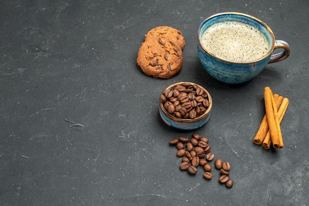 Vista frontal de uma xícara de café com sementes de café, biscoitos de canela em um fundo escuro e isolado.