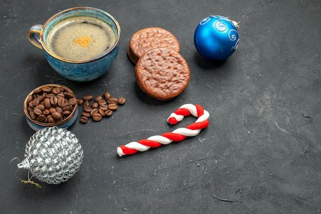 Vista frontal de uma xícara de café com sementes de café, biscoitos e detalhes de natal em um fundo escuro e isolado.