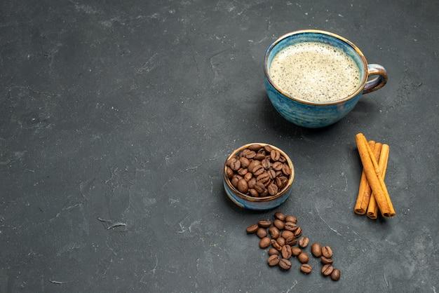 Vista frontal de uma xícara de café com sementes de café em bastões de canela em fundo escuro e isolado com espaço livre