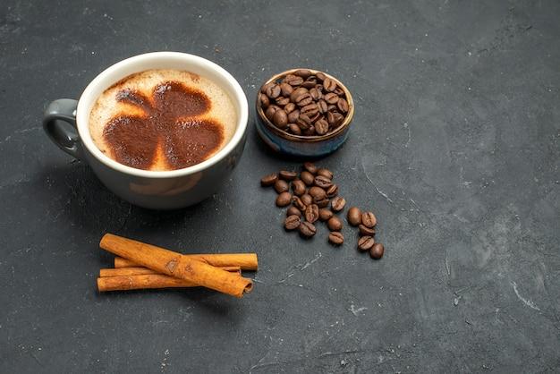 Vista frontal de uma xícara de café com sementes de café em paus de canela em um fundo escuro e isolado.