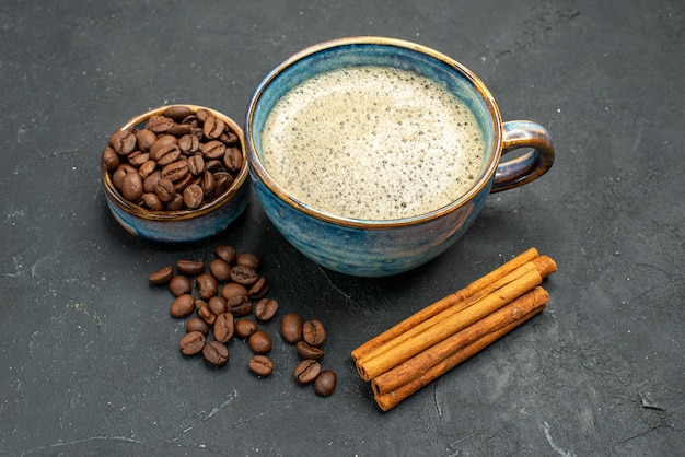 Vista frontal de uma xícara de café com sementes de café em paus de canela no fundo escuro isolado