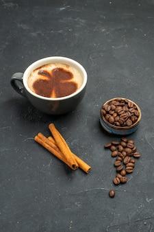 Vista frontal de uma xícara de café com sementes de grãos de café em bastões de canela em um fundo escuro isolado.