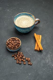 Vista frontal de uma xícara de café com sementes de grãos de café em bastões de canela no fundo escuro isolado