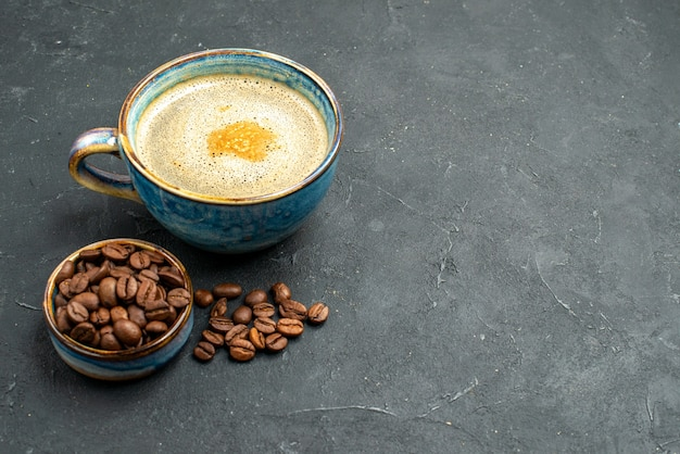 Vista frontal de uma xícara de café com sementes de grãos de café em um local escuro