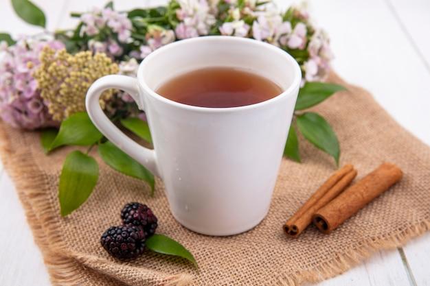 Vista frontal de uma xícara de chá com canela e flores em um guardanapo bege